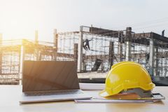 Safety helmet and computer laptop on table in concstruction. Site stock photos
