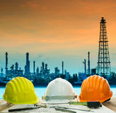 Safety helmet on engineer working table against beautiful oil re Stock Image