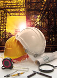 Safety helmet on engineer working table against pipe line struct Stock Photography