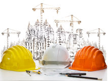 Safety helmet on engineer working table against sketching of building construction and high crane Royalty Free Stock Photography