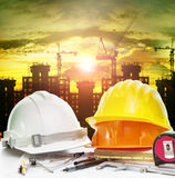 Safety helmet on engineer working table and construction site ba Royalty Free Stock Image
