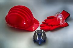 Safety helmet and others useful tools for self protection on a gray textured surface Royalty Free Stock Photos