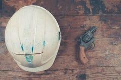 Safety helmet and revolver Stock Photos