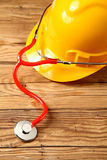 Safety Helmet with Stethoscope on Wooden Table Stock Photos