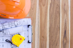 Safety helmet and tape measure over a construction plan Royalty Free Stock Photography