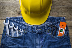 Safety helmet and tools set in a jeans pocket Royalty Free Stock Photography