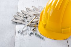 Safety helmet and tools. Yellow safety helmet and tools on white wooden table royalty free stock photo