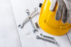 Safety helmet and tools. Yellow safety helmet and tools on white wooden table stock photo