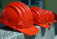 Safety helmets. (red hard hats for protection) on a construction site placed in a row Royalty Free Stock Photos