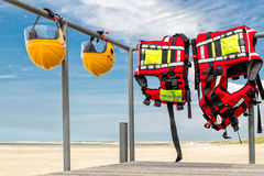 Safety helmets and life jackets hanging on railing Stock Images