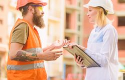 Safety inspector concept. Woman inspector and bearded brutal builder discuss construction progress. Construction site royalty free stock photos
