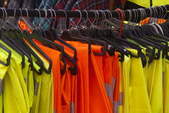 Safety Jackets and Trousers on  hangers. Rail of hangers with hiviz safety vest jackets or tabards made of reflective yellow dayglo material Royalty Free Stock Photo