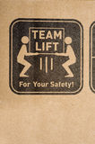 Safety Label on Box. A safety label on a cardboard box instructing to team lift Stock Image
