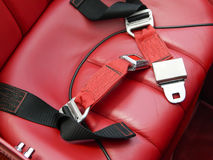 Safety lap belts on red leather car seat Stock Images
