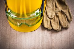 Safety leather gloves hard hat and plastic glasses on wooden boa Stock Photos