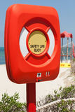 Safety life buoy in plastic case on the beach Stock Images