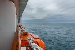 Safety lifeboat on deck of a cruise ship. Bad weather condition. Stock Image