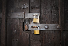 Safety Locks. Two golden Safety Locks on an old, wooden door, close up royalty free stock photography