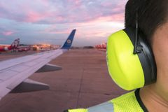 Safety male worker controlling aircraft and writing information.  Royalty Free Stock Photos