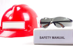 Safety manual. Safety eyeglasses on a safety manual book and safet helmet Stock Photos