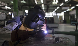 Safety mask welding metal. Worker wearing safety mask welding metal in factory Stock Photography