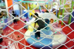 Safety mesh for children at indoor playground with blurred focus. Background royalty free stock images