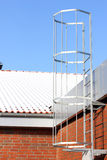 Safety metal ladder to the roof and blue sky Stock Photo