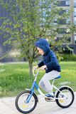 Safety in a modern European city. A little happy boy rides a bicycle through a closed courtyard in a multi-storey urban. Building royalty free stock image