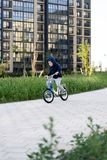 Safety in a modern European city. A little happy boy rides a bicycle through a closed courtyard in a multi-storey urban. Building royalty free stock photos