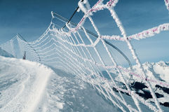 Safety net on ski run in italian alps. Frozen and snow covered protective net on skiing track, italian alps Stock Images