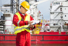 Safety officer. Standing in front of a huge industrial platform, wearing overalls, a hard hat, safety goggles, and holding a clipboard with checklists Royalty Free Stock Images