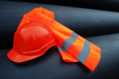 Safety orange worker helmet at steel pipes.  Stock Photo