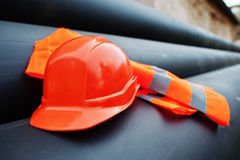 Safety orange worker helmet at steel pipes.  Royalty Free Stock Photography