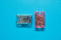 Safety pins in blue and pink plastic boxes on blue background. The safety pin is a variation of the regular pin which includes a simple spring mechanism and a stock photography