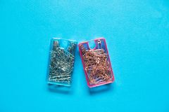 Safety pins in blue and pink plastic boxes on blue background. The safety pin is a variation of the regular pin which includes a simple spring mechanism and a stock photos