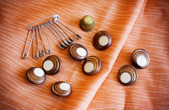 Safety pins and  buttons. On biege cloth Stock Photography