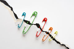 Safety Pins And Disrupt Paper. Set of color safety pins attached to disrupt white paper Royalty Free Stock Images