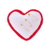Safety pins pierce plush heart isolated on white Royalty Free Stock Photos