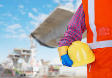 Safety Protective Work Equipment. Worker in orange vest holding yellow helmet Royalty Free Stock Image