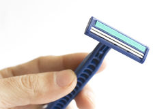 Safety razor. Isolated blue safety razor in hand Stock Photography