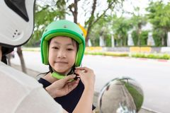 Safety riding concept.Mother trying to wear a bike helmet to his stock photography
