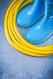 Safety rubber boots garden hose on metallic background gardening. Concept royalty free stock photos