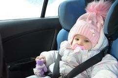 Safety seat for baby in car. Little cute girl in a pink hat and overalls sits winter in a child fastened with straps. stock photo