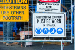 Safety and security on construction site. Warning signs on fence at construction site with symbols for compulsory protective gear to enter, legs of worker in stock photo