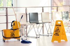 Safety sign with phrase Caution wet floor and mop bucket, indoors. Cleaning service stock image