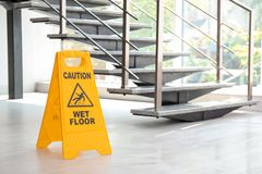 Safety sign with phrase Caution wet floor near stairs. Cleaning service royalty free stock image