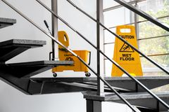 Safety sign with phrase Caution wet floor. And mop bucket on stairs. Cleaning service stock photo