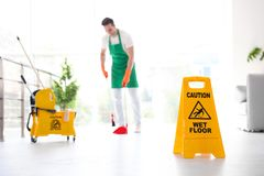 Safety sign with phrase CAUTION WET FLOOR and young worker on background royalty free stock photo