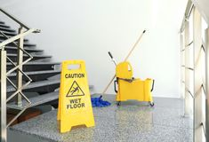 Safety sign with phrase. `CAUTION WET FLOOR` and mop bucket on stairs. Cleaning tools stock photography