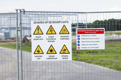 Safety signs. Shield with safety signs on a fence at a construction site Royalty Free Stock Photo